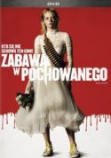 """Zdjęcie okładki filmu: """"Stojąca Kobieta ubrana w białą suknię z przewieszoną przez ramię ładownicą z bukietem kwiatów w dłoni"""""""