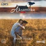 """Zdjęcie okładki audiobooka Grażyny Jeromin-Gałuszka, pt. """"Aksamitka"""" - młoda kobieta uczepiona szyi młodzieńca niosącego ją na placach."""