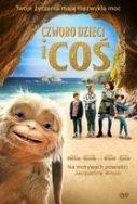 Zdjęcie okładki filmu: stwór podobny do małpki wszedł w kadr pozujących do zdjęcia dzieci na plaży