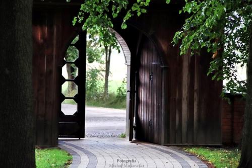 Zabytkowa drewniana brama prowadząca do kościoła w Bardzicach.
