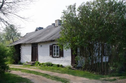 Piaszczysta droga prowadząca do starej, drewnianej, pobielonej chatki chłopskiej.