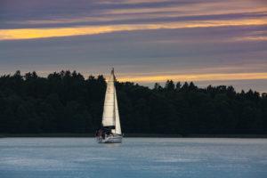 Jacht z postawionymi żaglami spokojnie żegluje o zmroku na wodach Jeziora Mamry - w oddali widać ścianę lasu.