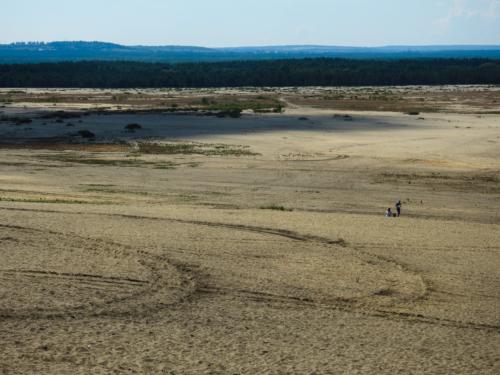 Małe postacie dwojga ludzi na rozległej Pustyni Błędowskiej.