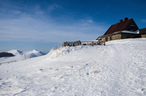 Ośnieżony szlak górski prowadzący do schroniska Chatka Puchatka na Połoninie Wetlińskiej w Bieszczadach - w oddali widoczne zaśnieżone pasmo gór.