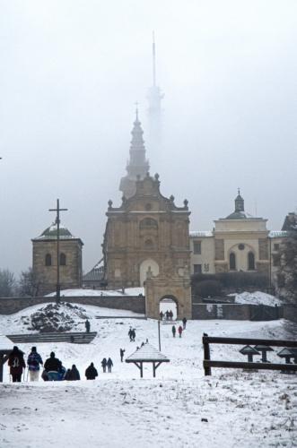 Klasztor Misjonarzy Oblatów na Świętym Krzyżu w zimowej scenerii w tle majaczy spowity mgłą nadajnik wieży telewizyjnej