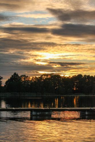 Złote refleksy świetlne zachodzącego słońca odbijające się na tafli Jeziora Sztynorckiego.