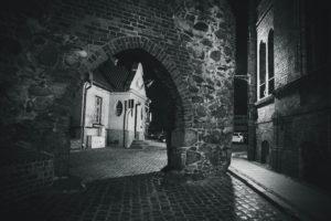 Czarno-białe zdjęcie średniowiecznej zabudowy uliczki Starego Miasta w Toruniu, na której końcu znajduje się brama w kształcie łuku.