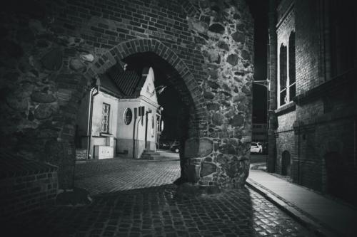 Czarno-białe zdjęcie średniowiecznej uliczki w Toruniu na której końcu znajduje się brama w kształcie łuku.