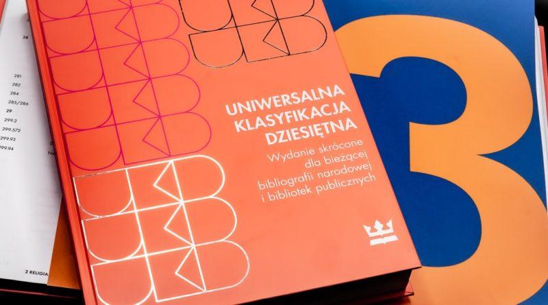 Baner informacyjny z tekstem: UNIWERSALNA KLASYFIKACJA DZIESIĘTNA Wydanie skrócone dla bieżącej bibliografii narodowej i bibliotek publicznych.