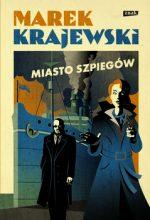 """Zdjęcie okładki książki, pt. """"Miasto szpiegów"""" - rysunek młodej kobiety w płaszczu odwróconej tyłem do tajemniczego mężczyzny."""